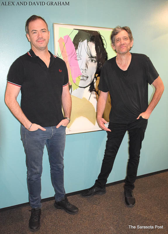 David and Alex Graham posing with Andy Warhol's Mick Jagger that was gifted to their father Bill Graham.