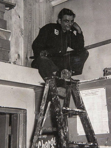 Sande Caplin's dad on a ladder painting his gas station.
