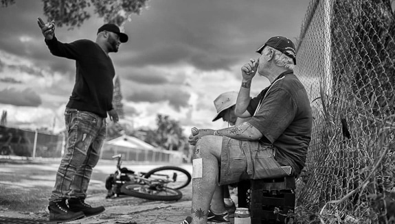 Greg Cruz, President of Streets of Paradise,  talks with some of his street friends in Sarasota FL