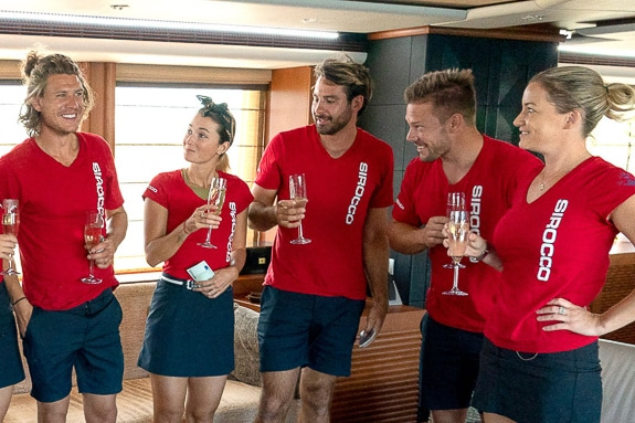 The crew on the reality show Below Deck celebrate after a well-run cruise.