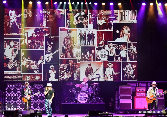 The bands' 80's videos play on the big screen as they perform.