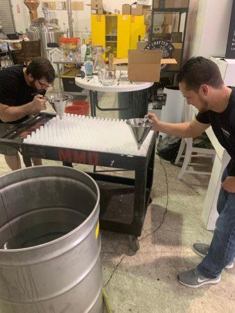 Brandon Marshall and Barry Elwonger filling sanitizer bottles.