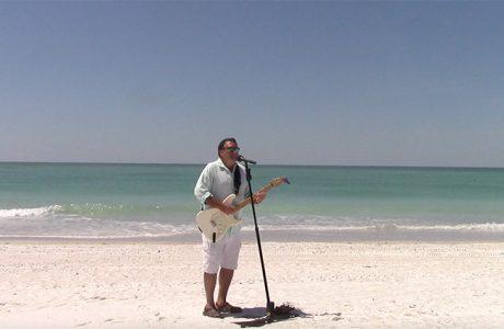 local suncoast musician wilth guitar and microphone on a beach