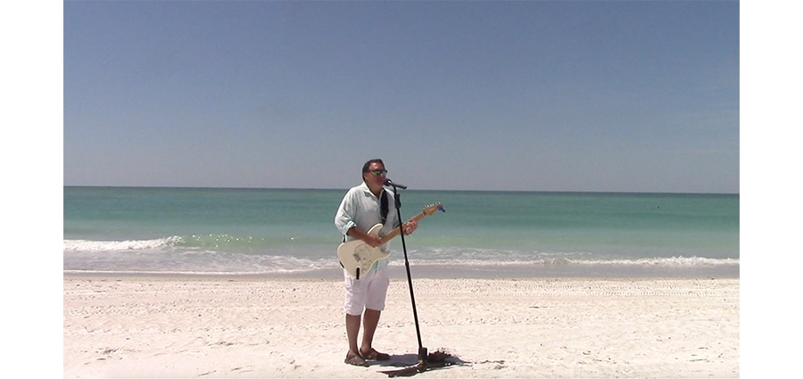 local suncoast musician wilth guitar and microphone on a beach