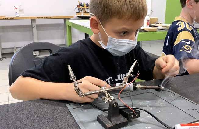 It's electric! Electronics STEM Saturday student is wowed as he learns how to solder a circuit.